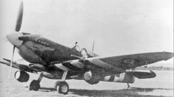A Spitfire IX bearing D-Day invasion stripes, and carrying beer casks beneath its wings, on the ground. It is probably significant that in none of the shots of beer-carrying aircraft can the identifying letters be seen: therse were almost certainly all publicity shots
