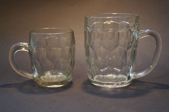 One-pint and half-pint glass mugs with a hexagonal tiled design, stamped 'GR 64' for Newcastle upon Tyne. Did this design inspire the dimple?