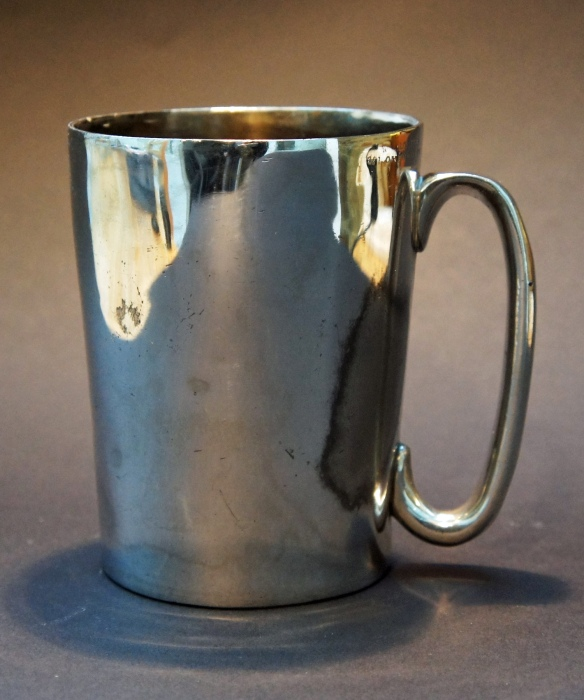 One-pint silver-plated pewter mug, stamped  'W Loftus 321 Oxford Street' and engraved on the bottom 'Sloanes Head New St Brompton Rd'. Loftus was a well-known pewterer, and also a 'Hydrometer, Saccharometer, and gauging instrument maker, to the Government, and manufacturers of bottling and corking machines and all utensils for the spirit and brewing trades'. He was based at 321 Oxford Street from around 1880 to around 1900. The Sloanes Head was at 16 New Street from at least 1839, when it was the Sir Hans Sloane's Head. New Street became the top part of Hans Crescent in 1904: the pub seems to have been swallowed by the growth of Harrods about 1896