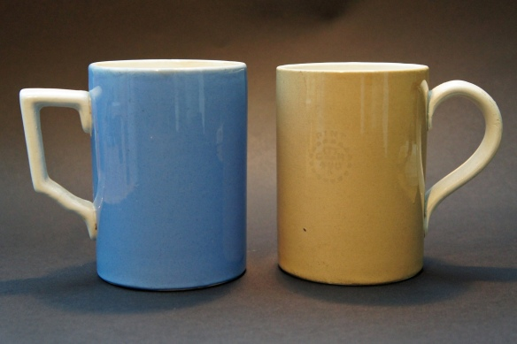 Two plain glazed pint pottery mugs, one with a baby blue exterior, the other biscuit-cream, both stamped 'GR 490' and made by Poultney & Co of Bristol