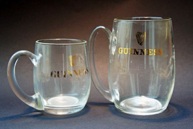 Two hand-blown Waterford Guinness glasses, made for the national roll-out of Draught Guinness in the 1960s. The half-pint version carries the Guinness name in the font known as Hobbs-face, itself designed specially for Guinness by Bruce Hobbs, art director at Guinness's ad agency, Bensons, in 1963. The glasses bear the official numbers 886 and 888, for Somerset, presumably where they were imported through from Ireland