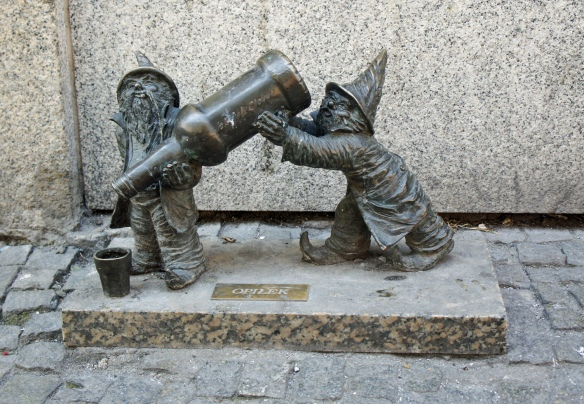 Two of the more than 300 bronze dwarfs to be found on the streets of Wrocław. They commemorate the surrealist anti-Communist Orange Alternative protest movement of the 1980s, whose symbol was a dwarf, and which started in Wrocław. 'Opiłek' means 'metal chip'